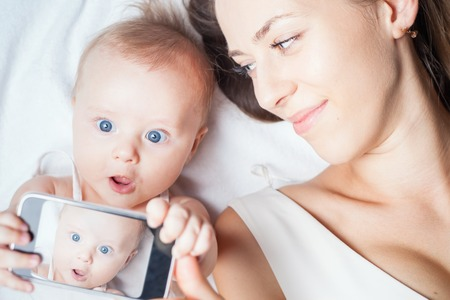 photo: Funny baby girl make selfie on mobile phone and lying near her mother on a white bed. Newborn looking at the camera and smiling. Mothercare is most important in baby life