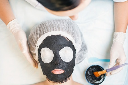 cosmetologist: Professional woman, cosmetologist in spa salon applying mud face mask. She is happy and looking up at camera. Concept of beauty, healthy therapy, rejuvenation, skincare and relaxing at luxury resort Stock Photo