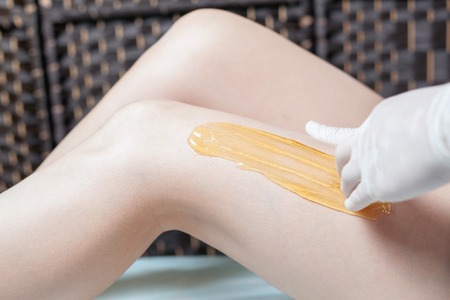 armpits: Sugaring epilation skin care with liquid sugar at legs. You can see her smooth and hair free armpits after hair removal. Stock Photo