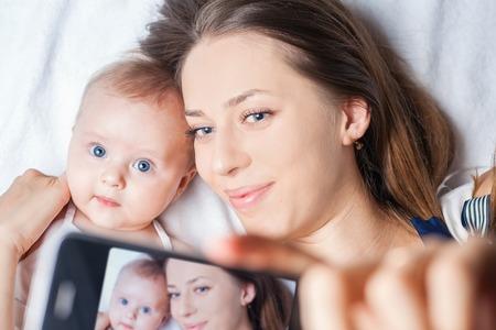 neonato: Bebé divertido hacer selfie en el teléfono móvil y situada cerca de su madre en una cama blanca. Recién nacido mirando a la cámara y sonriendo. Mothercare es más importante en la vida del bebé