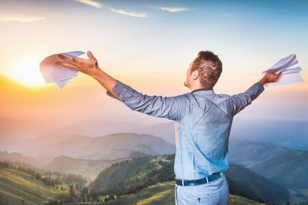 career: Image of a happy successful businessman who standing on the top of mountain and holding document paper. He looks into distance, thinking about future plans. Concept of professional career