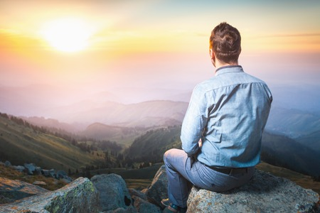 futurity: Image of a young businessman who sits on the top of the mountain and looks into the distance to the beautiful mountains, thinking about future plans Stock Photo