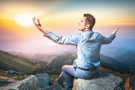 feels good: Image of a young businessman who sits on the top of the mountain and man feels good and imagines himself almighty Stock Photo