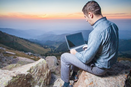 mountain valley: Image of a businessman on the top of the mountain, using a laptop. At the background there are beautiful panorama of valley with high peaks and beautiful sunset