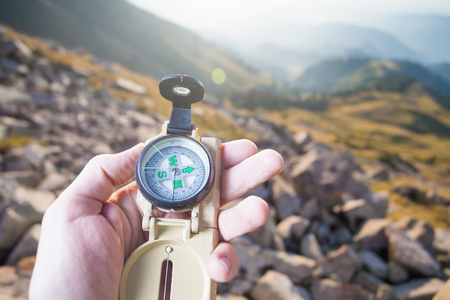 mountain valley: Picture of tourists hand using a compass. At the background a beautiful valley with tops of mountain. Switzerland.
