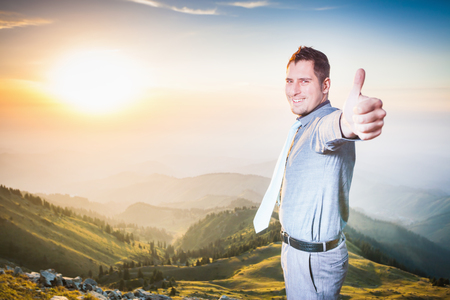 Image of successful happy businessman at top of mountain looking at camera with thumbs up gesture. Concept of professional career, achieve and success idea