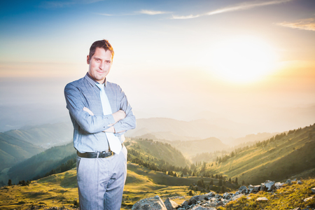 futurity: Image of successful businessman at top of mountain looking at camera. Concept of professional career and future plans in business, achieve and success for intelligent and handsome men Stock Photo