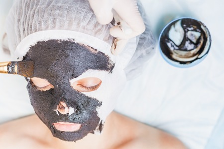 chocolate mask: Professional woman, cosmetologist in spa salon applying mud face mask. She is happy and looking up at camera. Concept of beauty, healthy therapy, rejuvenation, skincare and relaxing at luxury resort Stock Photo