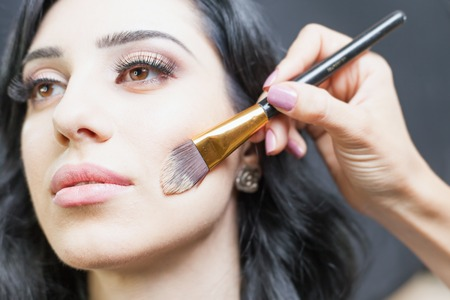 foundations: Beautiful arabian woman at beauty salon with a nice makeup. Make up artist apply foundation cream on face, holding in hands a makeup brushe on a dark or black background.