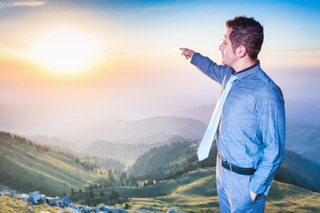 futurity: Image of successful happy businessman at top of mountain, he is pointing straight. Concept of professional career, achieve and success idea
