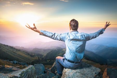 almighty: Immagine di un giovane imprenditore che si trova sulla cima della montagna e l'uomo si sente bene e si immagina onnipotente