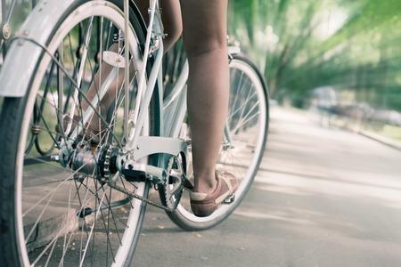 모션 블러 효과 도심에서 블루 빈티지 도시 자전거 타고 여자의 근접 촬영. 이 활동에 대한 개념과 건강한 라이프 스타일과 환경 친화적 인 교통 같다