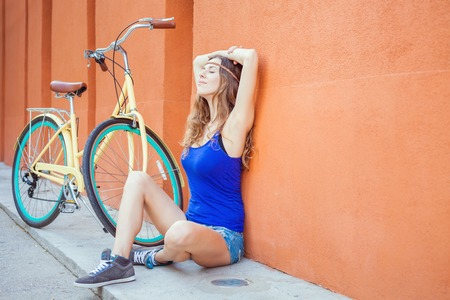 sexy girl sitting: Sexy beautiful caucasian woman sitting near the red wall background, there is a vintage city bicycle and copy space Stock Photo