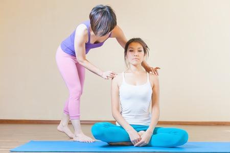 アジアのトレーナーは、屋内、ヨガのクラスでグループのヨガのクラスを行っています。健康的なライフ スタイルと生活に適切な態度の概念