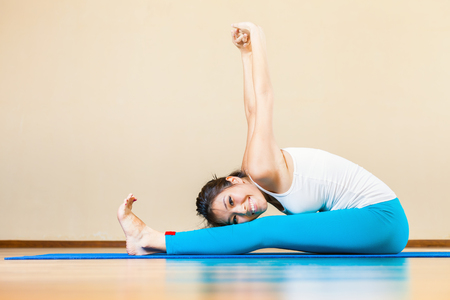haciendo ejercicio: Feliz y hermosa mujer asi�tica que hace ejercicio de yoga interior en casa. Ella mira a la c�mara y sonriendo. Concepto de una vida sana, el deporte y la actitud correcta para la vida