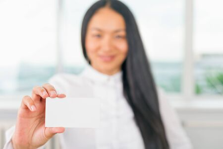 happy businesswoman: Happy and successful asian businesswoman gives you a business card or visiting card with a white background on a blank for copy space and any contacts or phone number