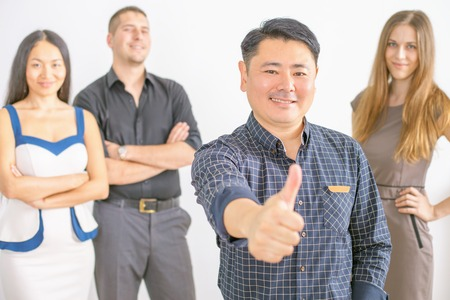 far off: Multiracial successful business people and mature asian boss with thumbs up gesture. They did it! Success is not far off! Stock Photo