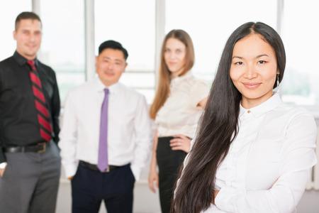 razas de personas: Exitosa mujer de negocios asi�tica con el pelo magn�fico larga y hay equipo de negocios en el fondo. Imagen simboliza una corporaci�n o empresa de �xito Foto de archivo