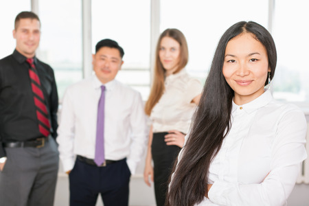 mixed race people: Successful asian business woman with magnificent long hair and there is business team at background. Image symbolizes a successful corporation or company