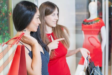 desired: Happy fashion women with bags talking about buying or new dresses or shoes indoor at the shopping center. One woman pointing at desired new dress! Stock Photo