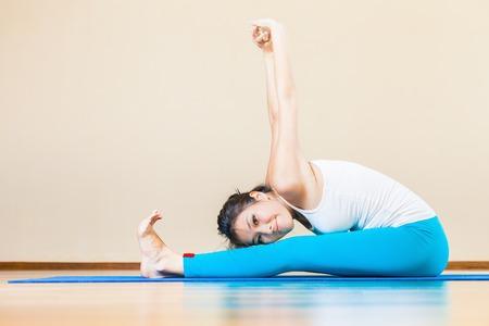 mujer meditando: Feliz y hermosa mujer asiática que hace ejercicio de yoga interior en casa. Ella mira a la cámara y sonriendo. Puede mantener los entrenamientos regulares en su casa de forma gratuita, estar sano y en buen tono! Foto de archivo