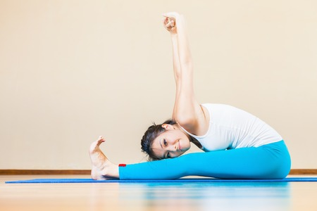 Happy and beautiful asian woman doing exercise of yoga indoor at home. She looking at camera and smiling. You can maintain regular workouts at your home for free, be healthy and in good tonus! Stockfoto