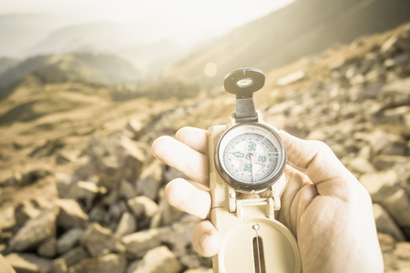 azimuth: Picture of tourists hand using a compass. At the background a beautiful valley with tops of mountain. Switzerland.