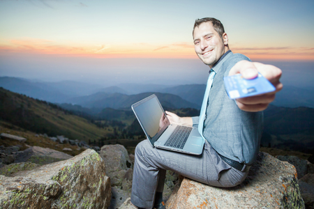 freelancing: Image of achieve and successful businessman on the top of mountain, using a laptop for online payment by plastic card through the Internet banking. He gives you a credit card