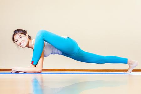 haciendo ejercicio: Feliz y hermosa mujer asiática que hace ejercicio de yoga interior en casa. Ella mira a la cámara y sonriendo. Concepto de una vida sana, el deporte y la actitud correcta para la vida