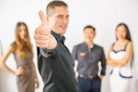 far off: Multiracial successful business people and young man with thumbs up gesture. They did it! Success is not far off! Stock Photo