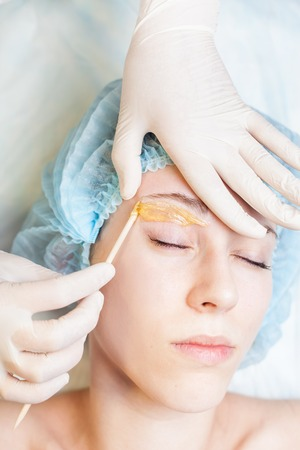 Closeup beautiful woman in spa salon receiving epilation or correction eyebrow using sugar - sugaring. You can see her smooth eyebrow after hair removal