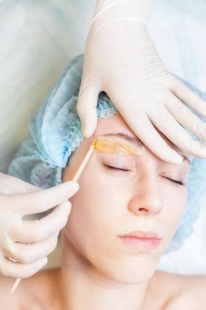 depilacion con cera: Mujer hermosa del primer en el salón de spa recibir la depilación o corrección de cejas usando azúcar - adición de sacarosa. Usted puede ver la ceja suave después de la depilación
