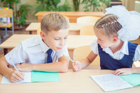 a study: Students or classmates in school classroom sitting together at desk. Boy writes off test at girl, he looking at her notebook. They are dressed in school uniforms. On table there is notebook and pen. Stock Photo