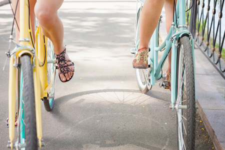건강한 라이프 스타일과 스포츠의 개념과 같은 빈티지 도시 자전거로 친구 타고 여성과 여행. 밑면, 전진 자전거
