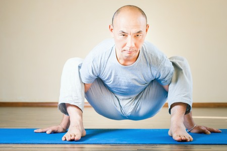 Inspired asian man in spider pose doing exercise of yoga indoor at class of yoga or home. Concept of a healthy lifestyle, sport and the right attitude to life.