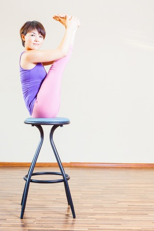 bar chair: Asian woman doing exercise or yoga at her home at bar chair.  Stock Photo
