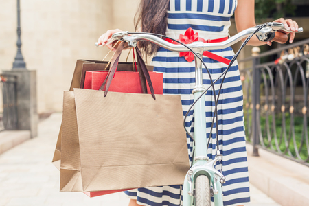 europe closeup: Closeup fashion woman dressed in striped dress with bags and vintage bike has shopping travel to Italy, Milan. She has happy vacation travel to Europe