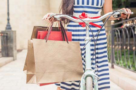 Vértes divat nő öltözött csíkos ruhában táskák és vintage kerékpár a bevásárló utazás Olaszországba, Milan. Ő boldog nyaralás utazás Európába