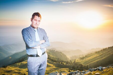 futurity: Image of successful businessman at top of mountain looking at camera. Concept of professional career and future plans in business, achieve and success with this handsome man Stock Photo