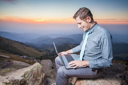 freelancing: Concept image of online payment by plastic card through the Internet Banking. Businessman on the top of the mountain, using a laptop.