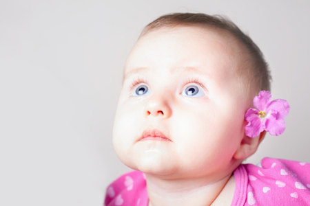 babycare: Portrait of a baby girl with blue eyes looking up in surprise at white background with copy space