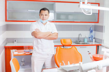 stomatological: Successful and confident dentist doctor at stomatological clinic with modern high-tech furniture design and professional instruments