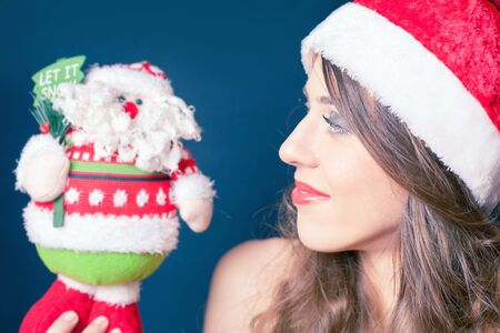 desired: Happy beautiful woman holding a toy of Santa Claus. Desired and successful gift at Christmas Eve or New Year