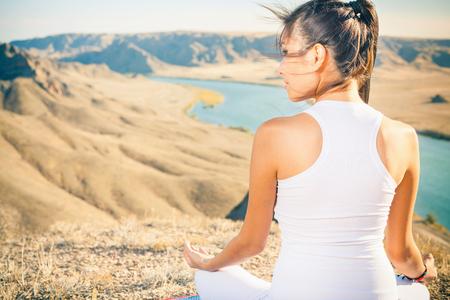 아름 다운 아시아 여자 휴식 및 중국에서 ILI 강 위의 산에서 야외 명상. 그녀는 로터스 위치에 산의 절정에 앉아 몸과 자연의 조화를 생각합니다. 몸과