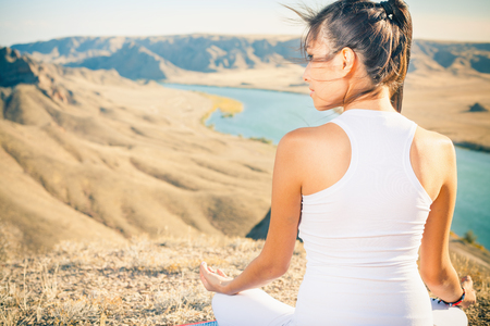 meditating: Beautiful asian woman relaxing and meditating outdoor at mountain above Ili river at China. She sits at peak of mountain in lotus position and feel harmony of your body and nature. Healthy lifestyles concept of body and soul