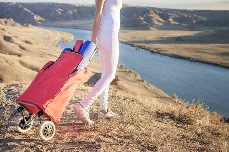 femme valise: Bonne femme asiatique transporte vos bagages avec tapis de yoga. Elle va jouer dans les sports ou exercices de fitness en plein air à la montagne. Modes de vie saine conception du corps et l'âme