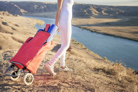 yoga mat: Happy asian woman carries your luggage with yoga mat. She going to play in sports or fitness exercises outdoor at mountain. Healthy lifestyles concept of body and soul