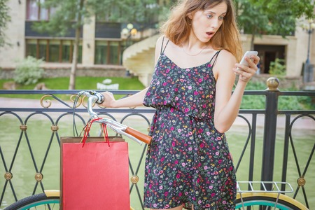 bugs shopping: Surprised caucasian woman with bugs using mobile phone or typing sms, near vintage bicycle. Her summer vacation in Italy, Milan for shopping and fun! Stock Photo