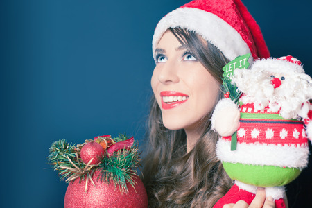 desired: Happy beautiful woman holding a toy of Santa Claus and tree decoration ball. Desired and successful gift at Christmas Eve or New Year