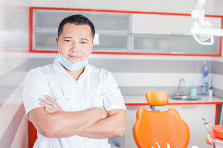 stomatological: Happy and confident dentist doctor at stomatological clinic with modern high-tech furniture design and professional instruments Stock Photo